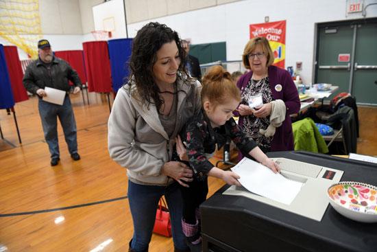 إمرأة تحمل إبنتها الصغيرة أثناء التصويت فى الانتخابات التمهيدية الأمريكية