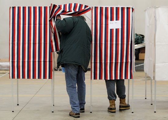 أحد الناخبين يدخل كشك الاقتراع لملئ استمارة التصويت