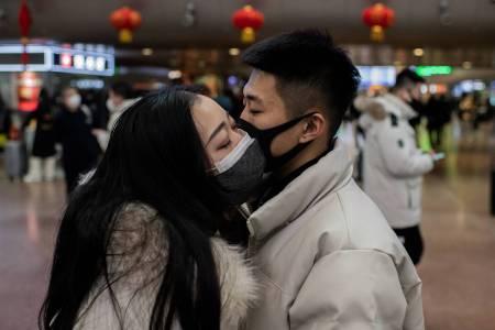 زوجان، يرتديان أقنعة واقية، يقبلون وداعًا أثناء سفرهم لقضاء عطلة رأس السنة القمرية الجديدة ، في محطة سكة حديد بكين الغربية في بكين في 24 يناير