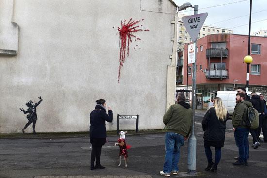 جانب من المواطنين يقفون أمام الجدارية