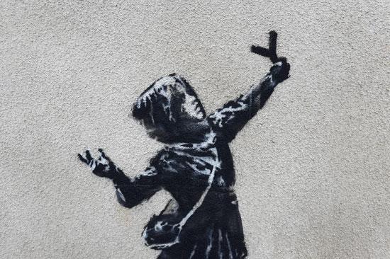 الجدارية تحمل صورة فتاة فى يدها مقلاع