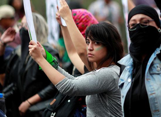 احدى المتظاهرات ترفع لافتة الاحتجاج