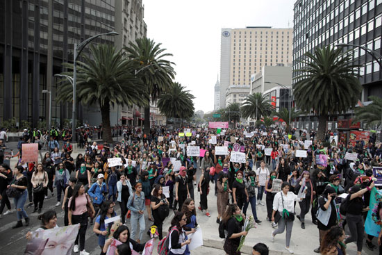 المتظاهرات يرفعن لافتات الاحتجاجات