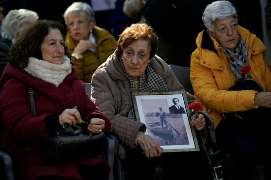 ميلاجروس مارتينيز تحمل صورة لوالدها وابنها أثناء دفن
