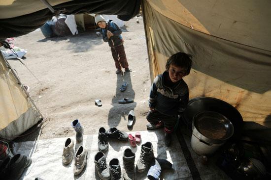 طفل من النازحين داخلياً يقف داخل خيمة في قرية قطمة