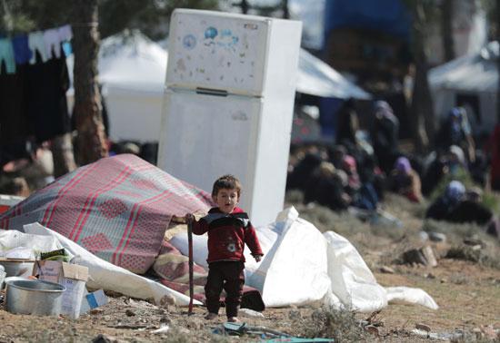 طفل نازح داخليًا يسير في مخيم مؤقت في قرية قطمة