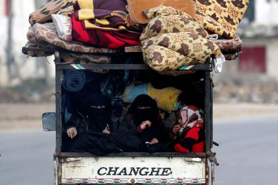 الأشخاص النازحون داخلياً يركبون شاحنة صغيرة مع أمتعتهم في عزاز