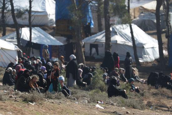 نساء وأطفال مهجرون داخلياً يجلسون خارج الخيام في قرية قاتمة
