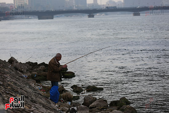 رجل يستمتع بحالة الجو امام النيل