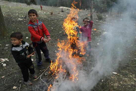 أطفال مشردون داخليًا يسخنون أنفسهم حول حريق في قرية القطمة