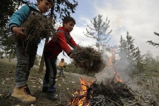 أطفال نازحون داخلياً يشعلون النار في مخيم مؤقت في قرية القطمة