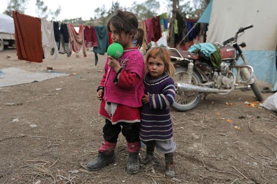 أطفال مشردون داخليا يقفون خارج الخيام في مخيم مؤقت في قرية القطمة