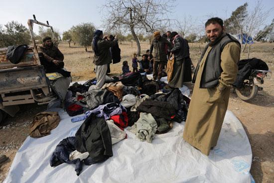 النازحون داخلياً ينظرون إلى الملابس المستعملة في مخيم مؤقت في قرية قطمة غرب عزاز