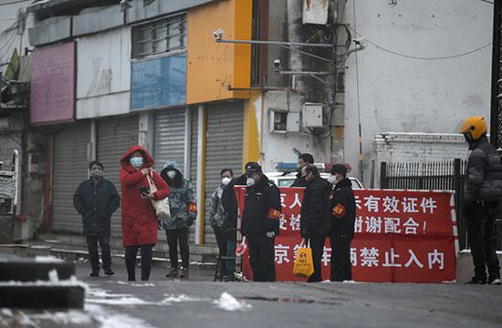 أفراد الأمن يقفون على مشارف قرية فى ضواحى بكين