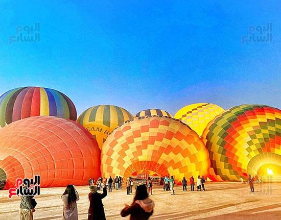 السائحون يلتقطون صورا تذكارية مع البالون
