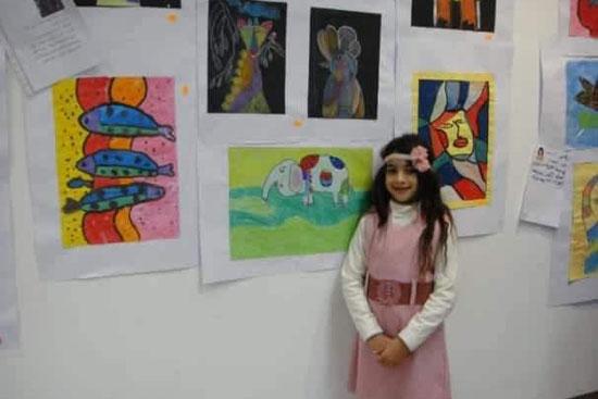 طفلة-بجوار-لوحاتها