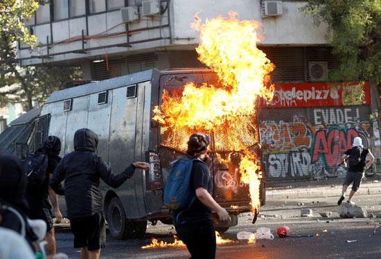 المتظاهرون يشعلون النار فى سيارة شرطة