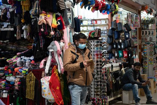 شخص يقف داخل السوق يرتدى الكمامة
