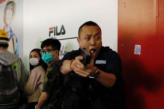 شرطى يوجه سلاحة للمحتجين