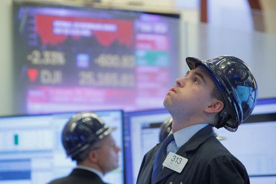 أحد المتداولين يرتدي خوذة وهو يعمل على الأرض في بورصة نيويورك للأوراق المالية