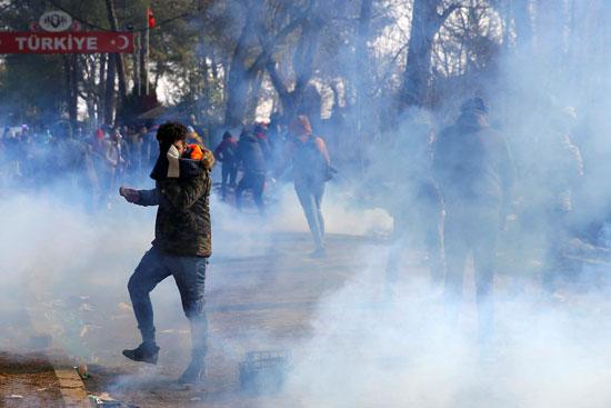 مهاجر يرمي أسطوانة غاز مسيل للدموع مرة أخرى خلال اشتباكات مع الشرطة اليونانية