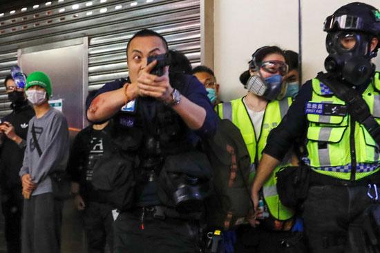 شرطى يوجه سلاحه للمتظاهرين