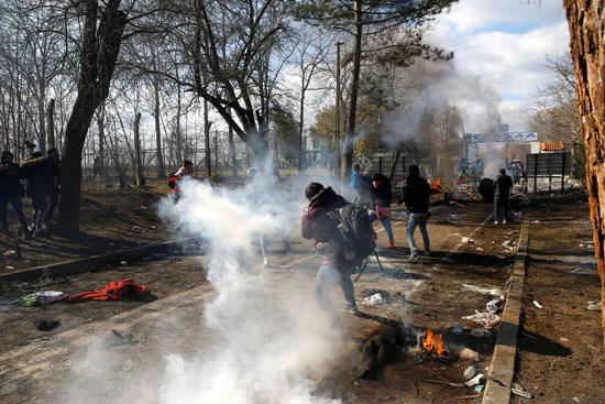 مهاجر يغطي وجهه بينما يطفو الغاز المسيل للدموع في الهواء