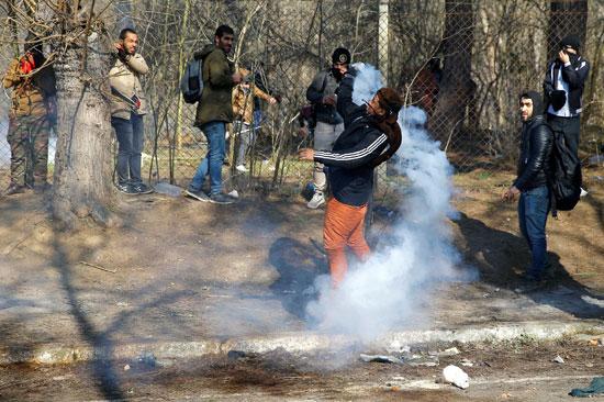 مهاجر يرمي أسطوانة غاز مسيل للدموع مرة أخرى خلال اشتباكات مع الشرطة