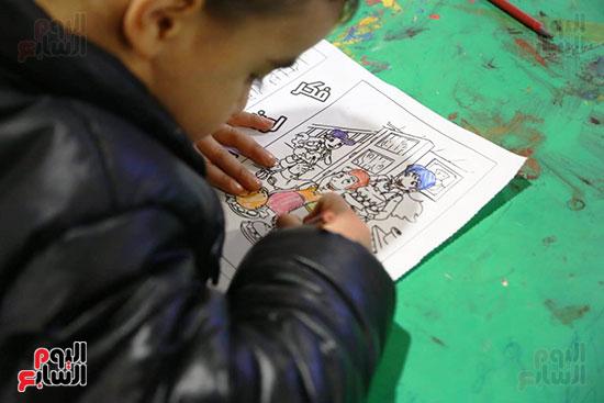 طفل يرسم فى ورش معرض الكتاب