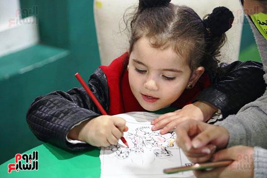 طفلة فى ورس الرسم بالمعرض