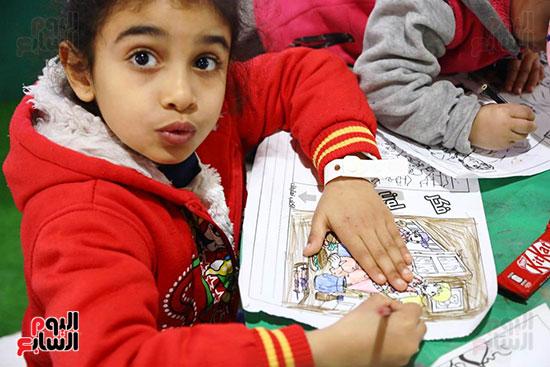 طفلة ترسم فى معرض الكتاب