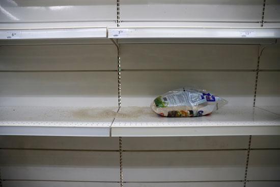 رف فارغ بينما يقوم الناس بتخزين المواد الغذائية