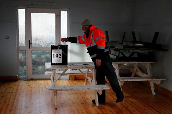رجل يدلي بصوته في مركز اقتراع في جزيرة إنيشبوفين