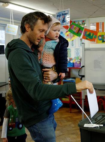 رجل يحمل طفلاً وهو يدلي بصوته في الانتخابات الوطنية الأيرلندية في كورك