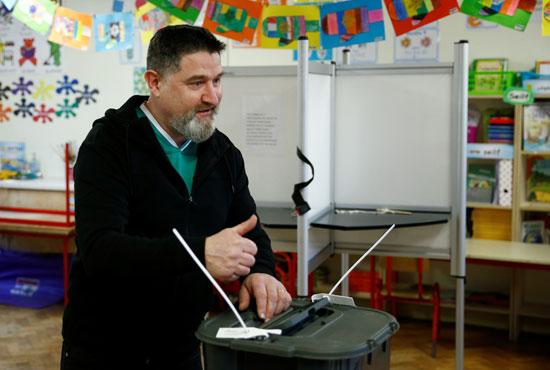 رجل يلمح وهو يدلي بصوته في الانتخابات الوطنية الأيرلندية في كورك