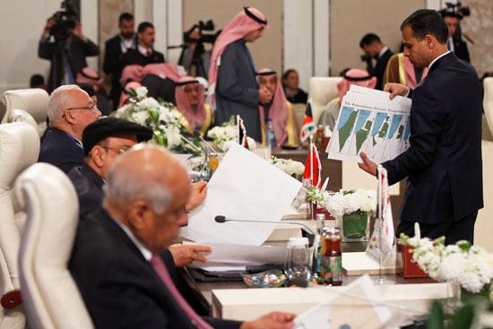 موظف يوزع الخرائط التاريخية لفلسطين على الوفود المشاركة خلال جلسة طارئة للبرلمانيين العرب