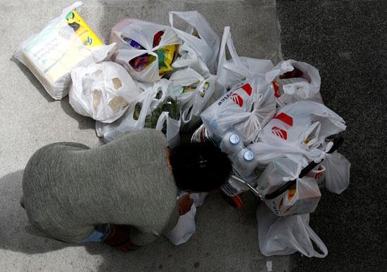 امرأة تحزم شرائها من مواد البقالة أثناء تخزينها للمواد الغذائية
