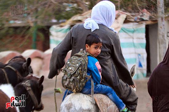 أب ينقل ابنه للمدرسة بالحمار