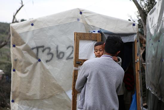 رجل يحمل ابنه خارج مخيم مؤقت للاجئين والمهاجرين بجوار مخيم موريا في جزيرة ليسبوس