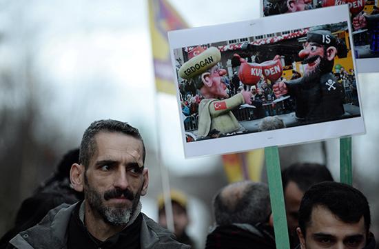متظاهر يحمل لافتة خلال مظاهرة مناهضة لزيارة الرئيس التركي قرب ميدان شومان في بروكسل