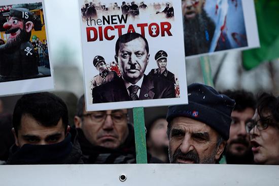 متظاهر يحمل لافتة تصور الرئيس التركي رجب طيب أردوغان خلال مظاهرة مناهضة لزيارة الرئيس ، بالقرب من ميدان شومان في بروكسل