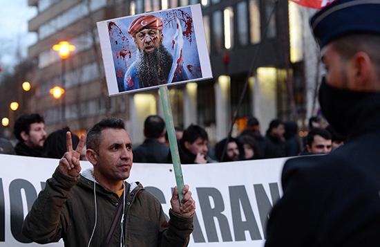 متظاهر يحمل لافتة تصور الرئيس التركي يتظاهر ضد زيارة الرئيس قرب ميدان شومان في بروكسل