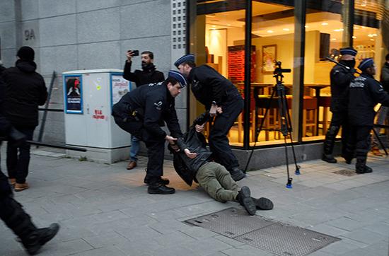 ضباط الشرطة يحتجزون متظاهرًا خلال احتجاج على زيارة الرئيس التركي رجب طيب أردوغان قرب ميدان شومان في بروكسل