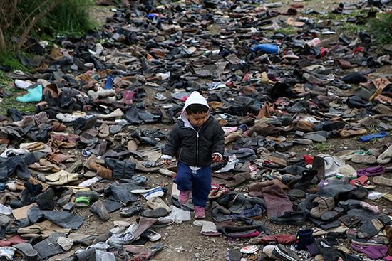 صبي يمشي بين أزواج من الأحذية بجوار مخيم موريا للاجئين والمهاجرين في جزيرة ليسبوس