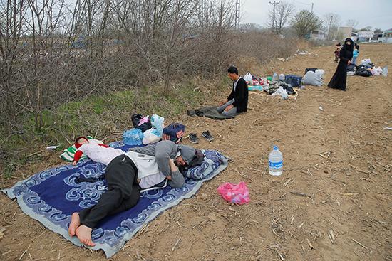 مهاجرون يستريحون قرب  حدود بازاركولي التركية في أدرنة