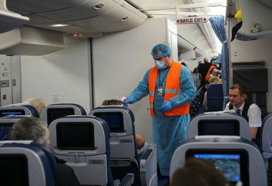 يقوم-المسؤولون-الطبيون-بفحص-الركاب-كإجراء-وقائي-ضد-فيروس-كورونا-في-مطار-خارج-كييف