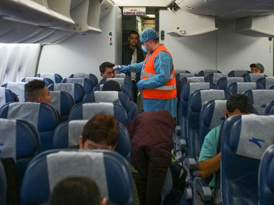 مسؤول-طبي-يفحص-الركاب-كإجراء-وقائي-ضد-فيروس-كورونا-في-مطار-خارج-كييف
