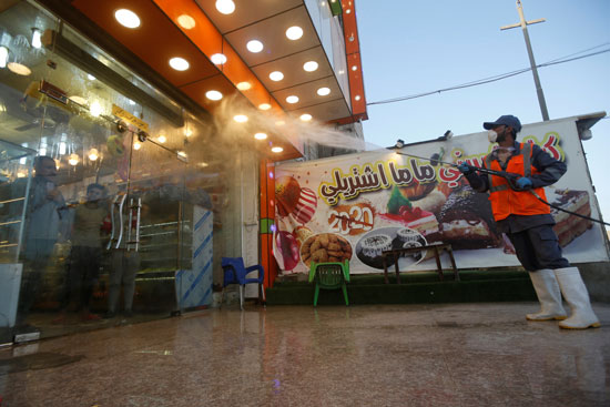 عامل-يرتدي-بدلة-واقية-يطهر-المطهرات-أمام-مطعم-في-أحد-الأسواق-الشعبية-في-البصرة