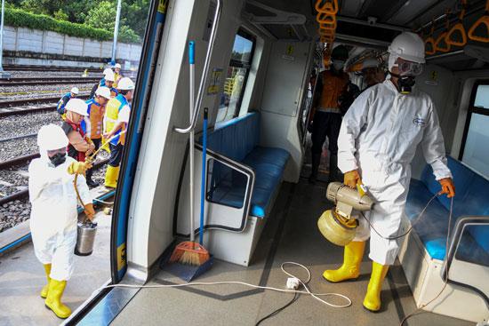 عاملون-يرتدون-بذلات-واقية-من-الرذاذ-المطهر-في-قطار-في-باليمبانج-،-جنوب-سومطرة