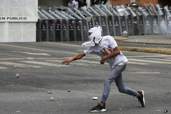 متظاهر يلقى الشرطة بالحجارة